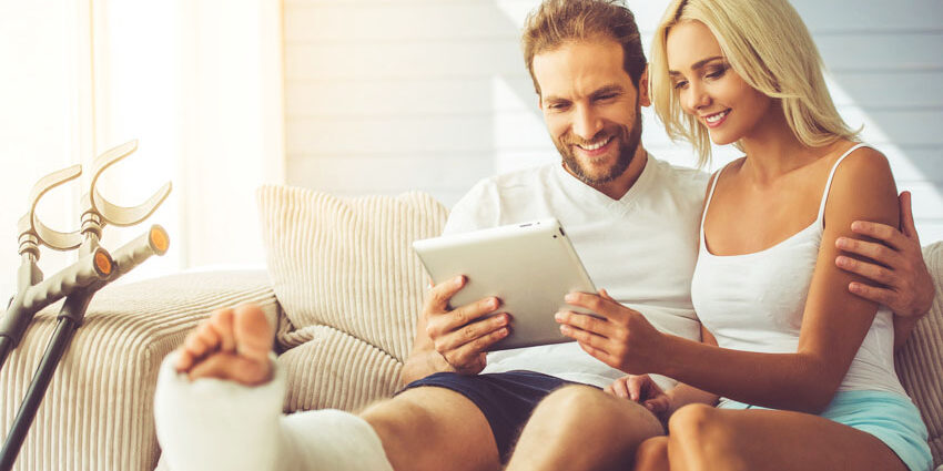 Handsome man with broken leg and his beautiful girlfriend are using a digital tablet and smiling while sitting on couch at home